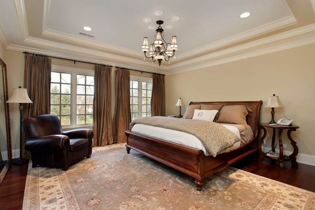 A rustic themed bedroom with a wooden dark varnished bed and brown curtains