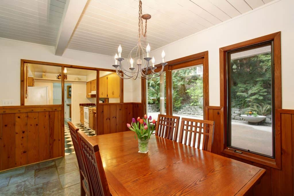 Rustykalny salon z żyrandolem z białymi malowanymi sufitami