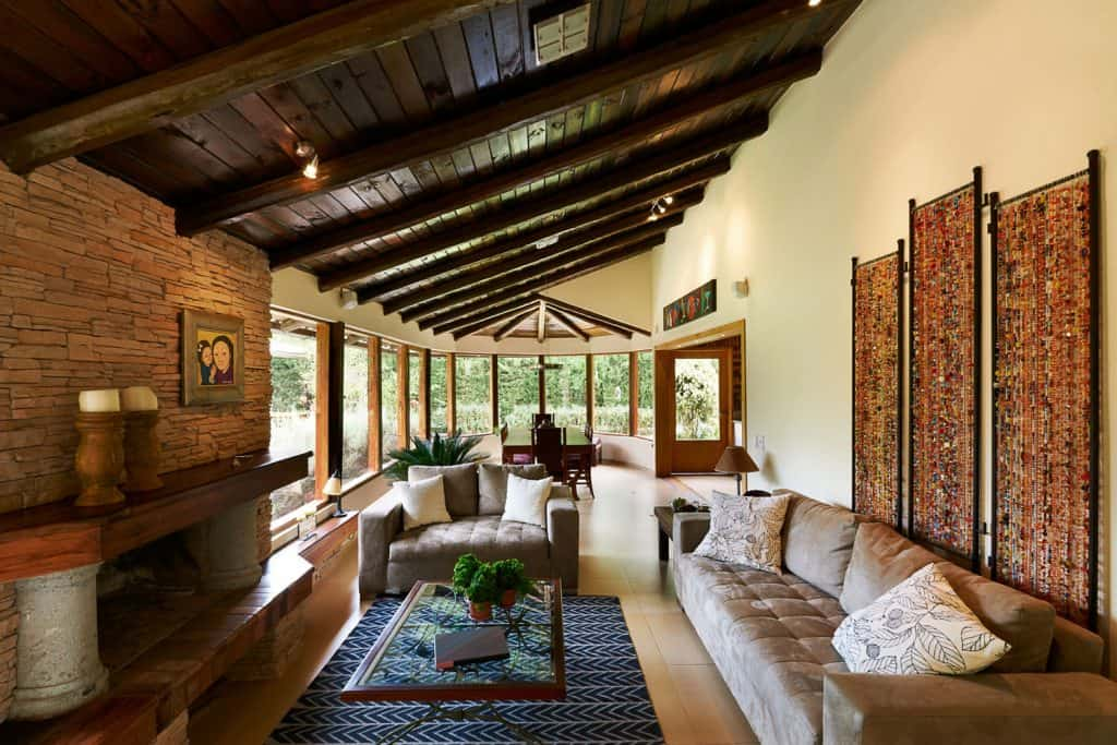 A rustic themed living room with dark painted wooden panels