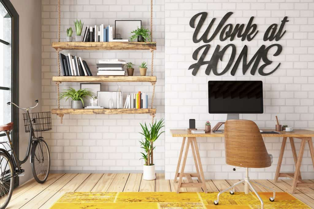 A rustic themed office are with a white painted brick wall and a wooden working table with a computer