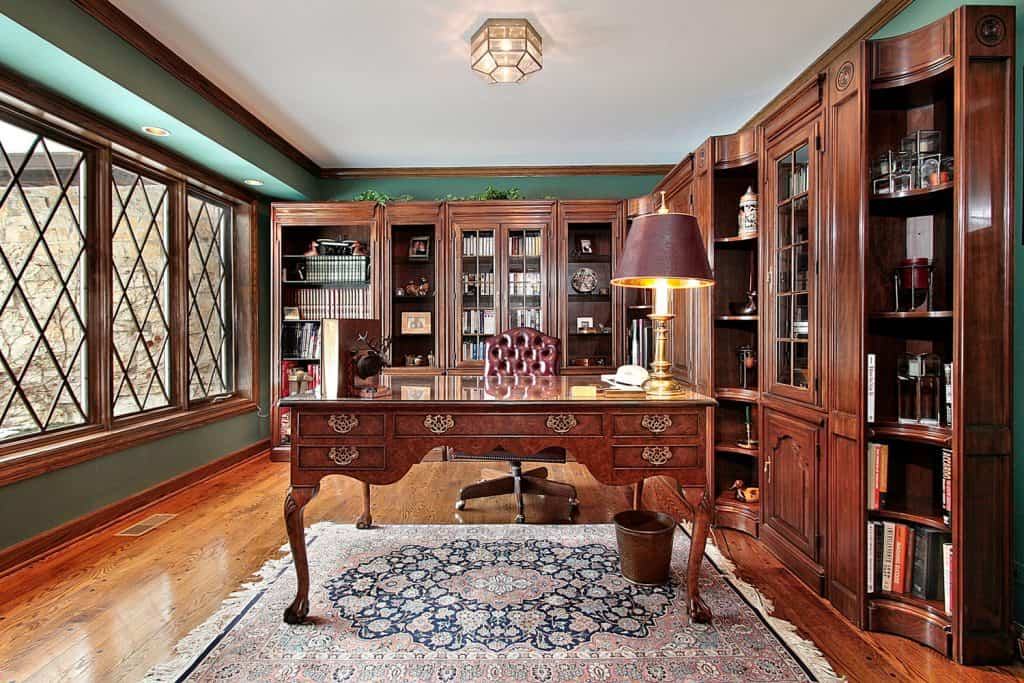 A rustic themed office are with wooden cabinets and table