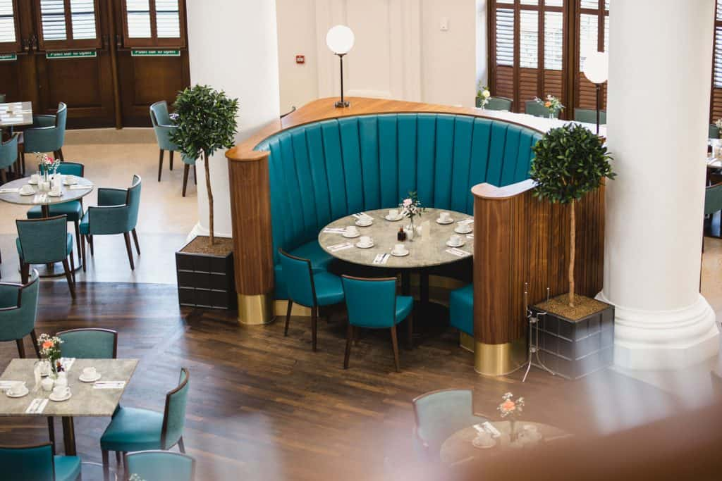 A semi-circular dining area of a restaurant with blue leather seats and wooden flooring