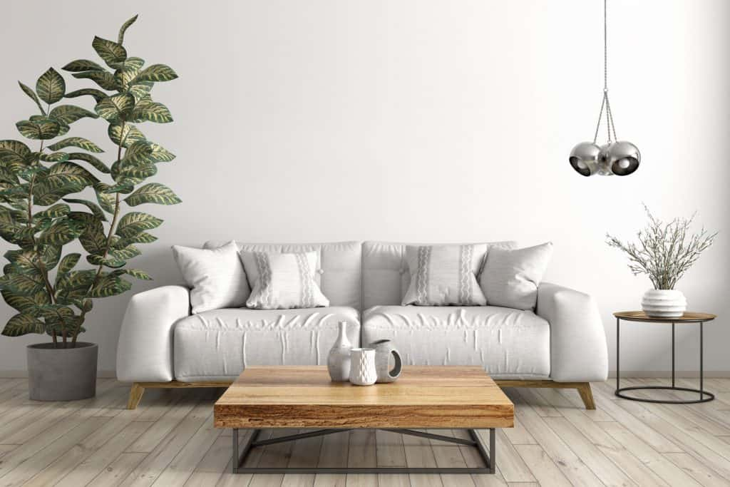 A simple minimalist themed living room with a wooden coffee table and a white sleeper couch inside a contemporary living room