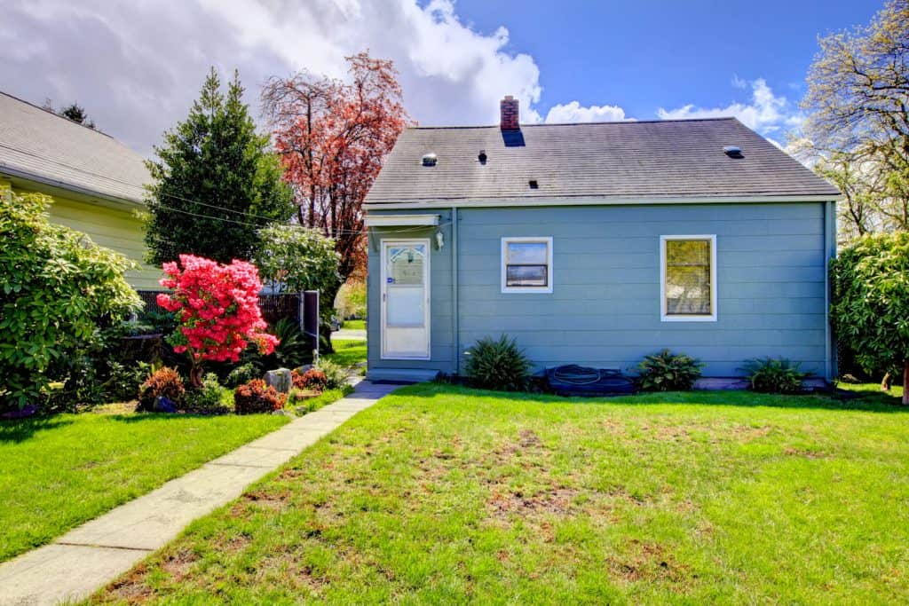 A small blue walled single family home with a small front lawn