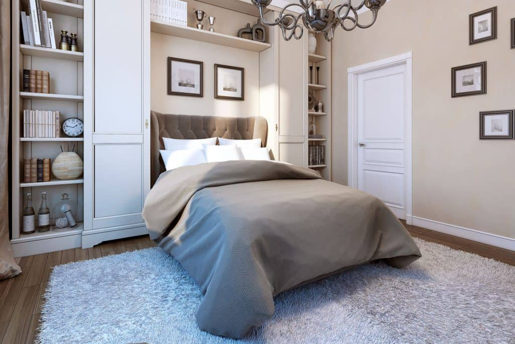 A small classic designed bedroom with a bed with gray beddings, cabinet, and picture frames hanged on a beige colored wall