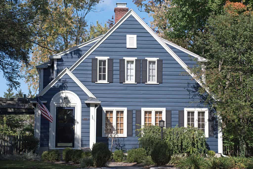 A small colonial house with blue painted sidings, white framed french windows, and a dark blue hardwood door