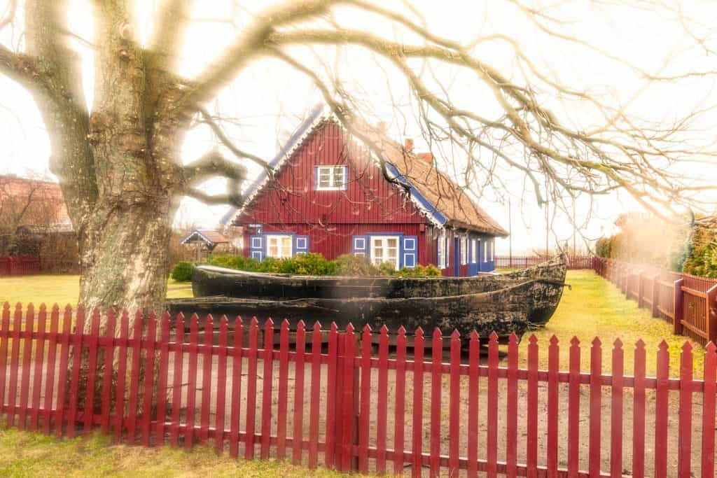 A small farmhouse with an old tree on the background with red painted fence