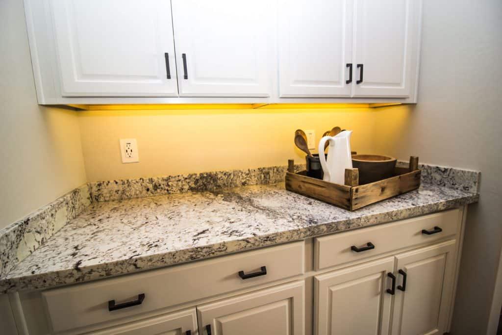 A small granite countertop with white cabinets