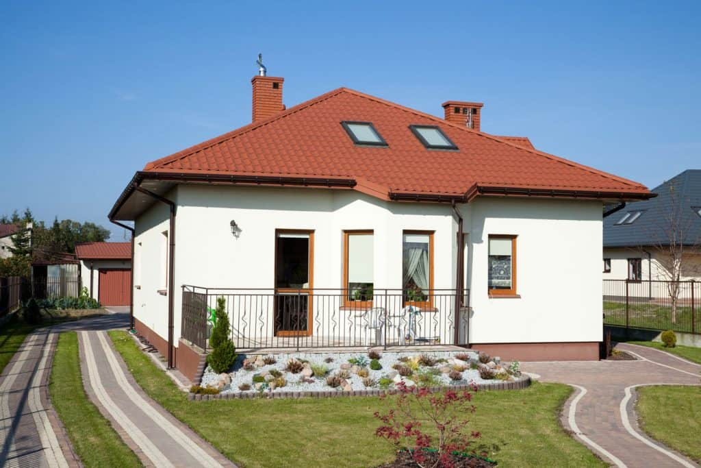 A small house with white painted wall and shingled roofing