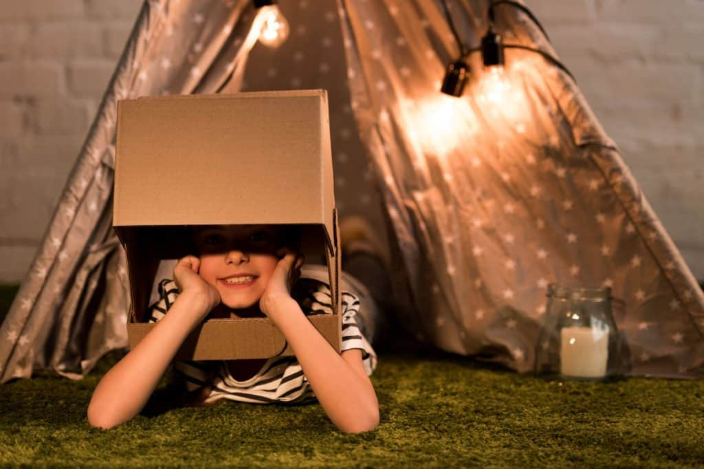 A small kid putting his head in a cardboard box with a tent on the background