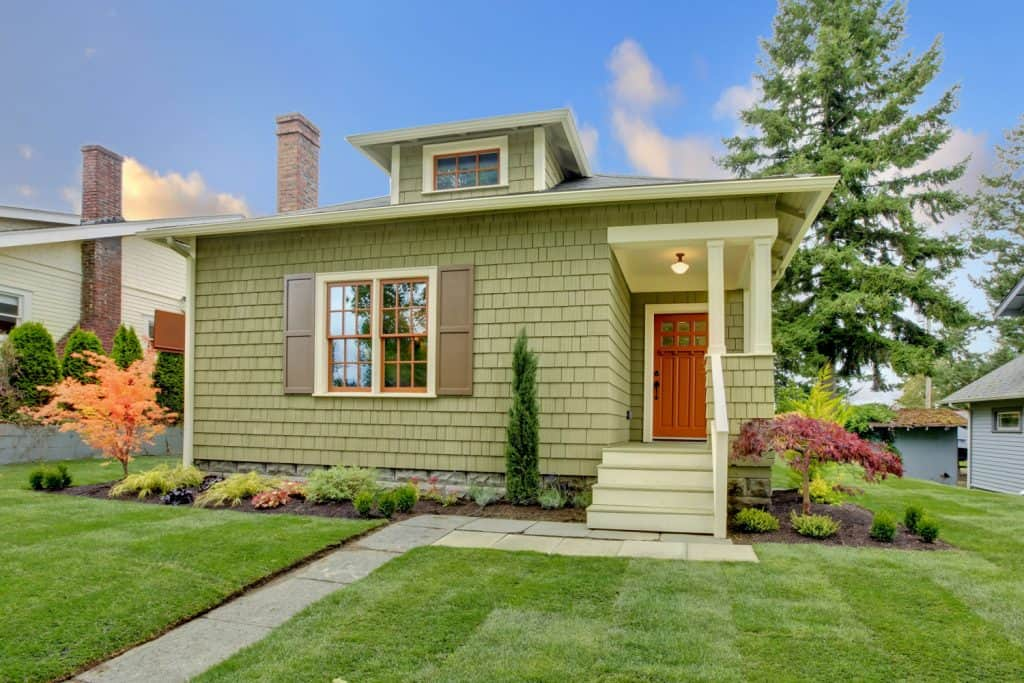 A small single family house painted in green with a beautiful paved lawn