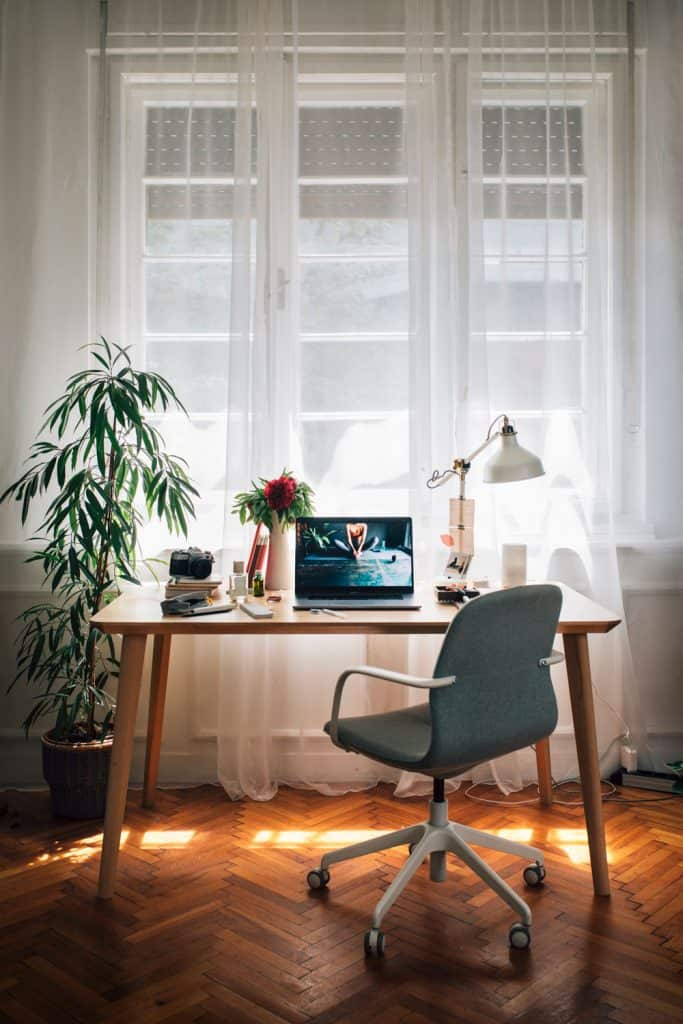 A small working table with a small laptop on it with a table plant on the left
