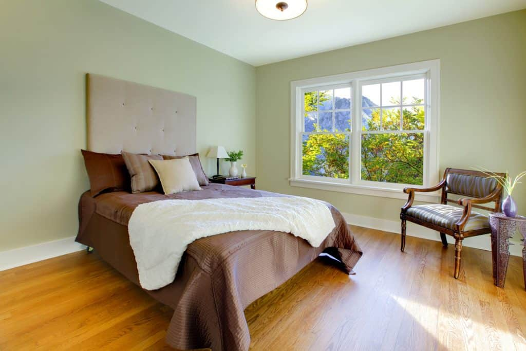A spacious bedroom with a brown bed with brown beddings and a wall painted in light green