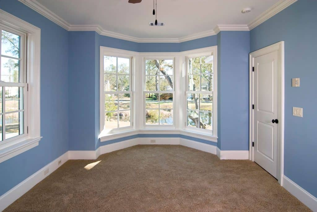 A spacious living room with blue walls, and window casings painted in white matching the door trim