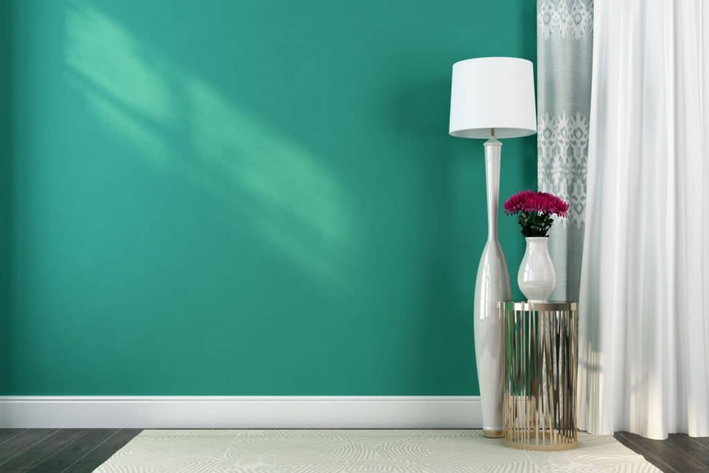 A teal green wall with a white curtain on the side and gray flooring with white rug