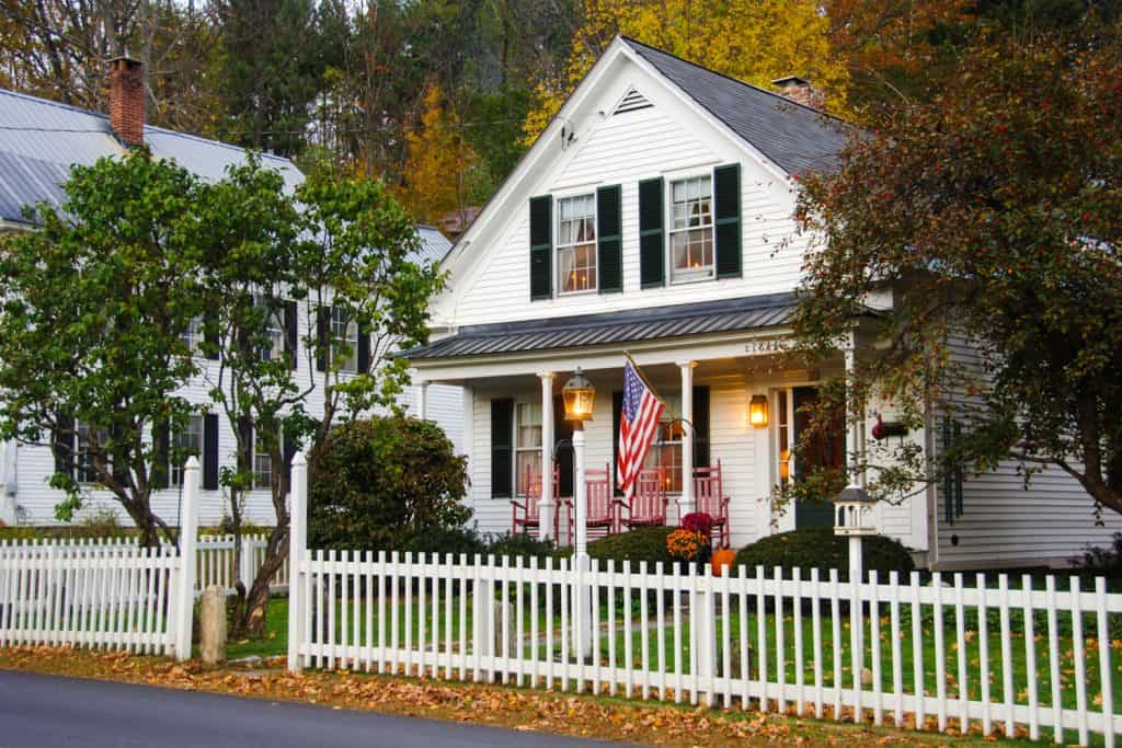 A traditional American colonial house with white painted wall and a white painted fence