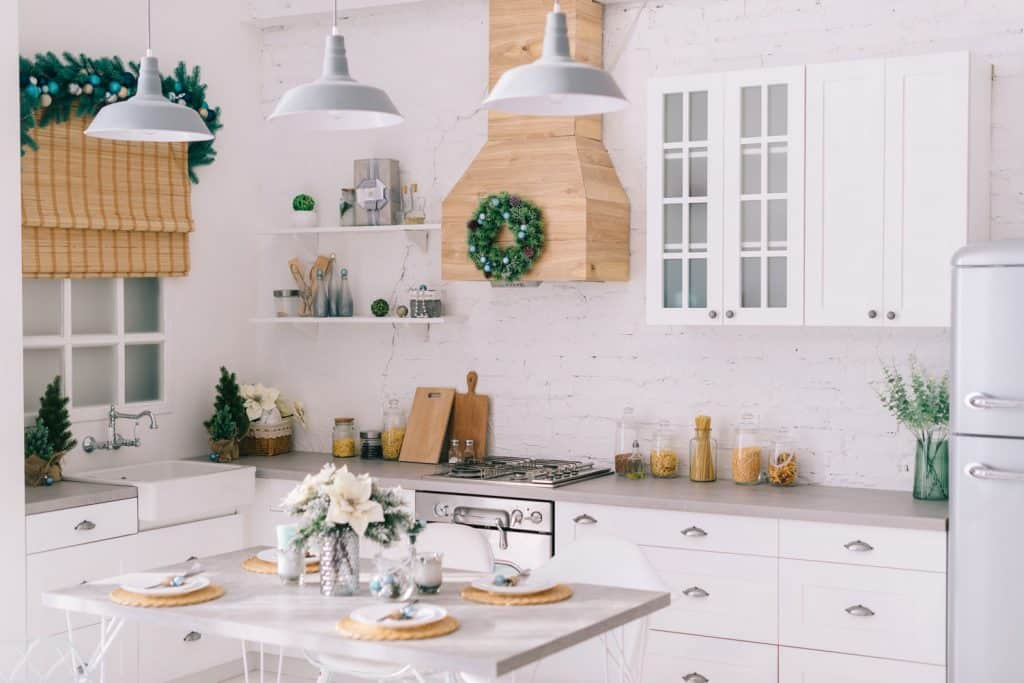 A vintage inspired kitchen with white cabinets and a wooden range hood