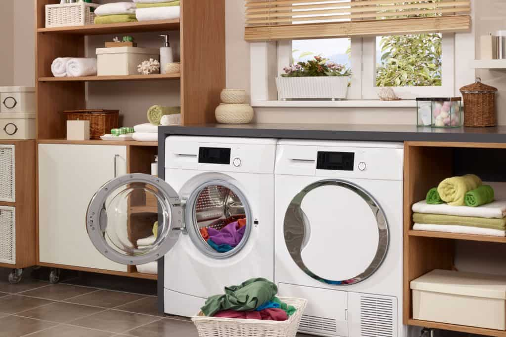A washing room of a house with washing equipment and wooden cabinets with washing materials