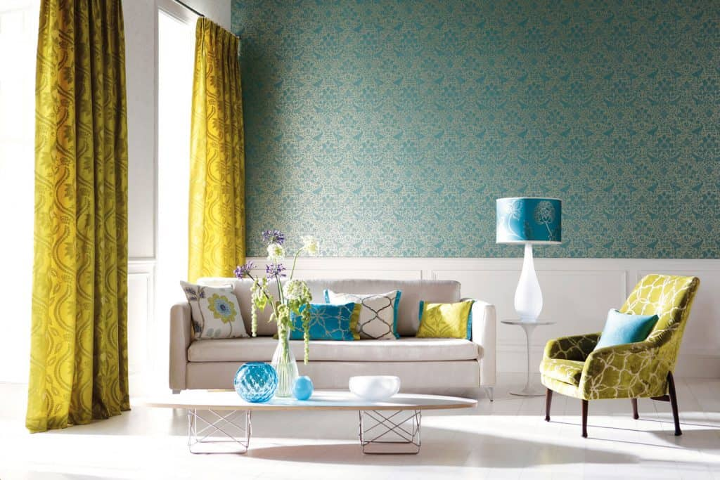 A well lit living room with light yellow curtains, blue patterned wall, a white baseboard, and a white couch