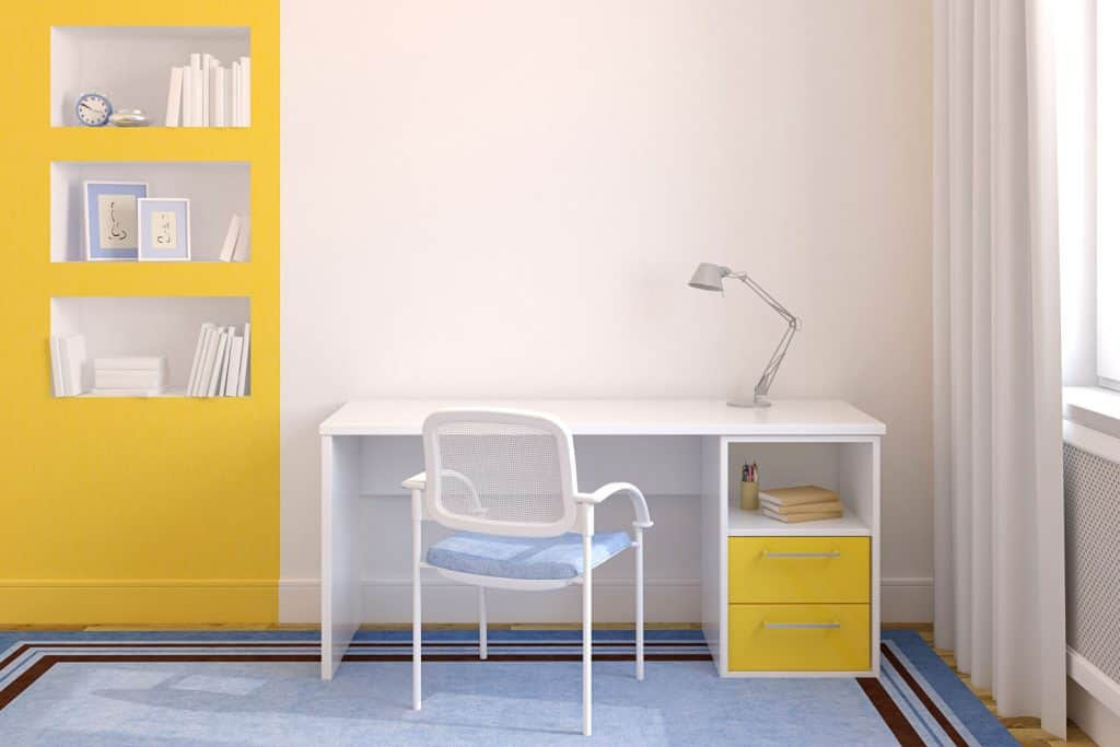 A white and yellow themed office with a white table and chair with a study lamp