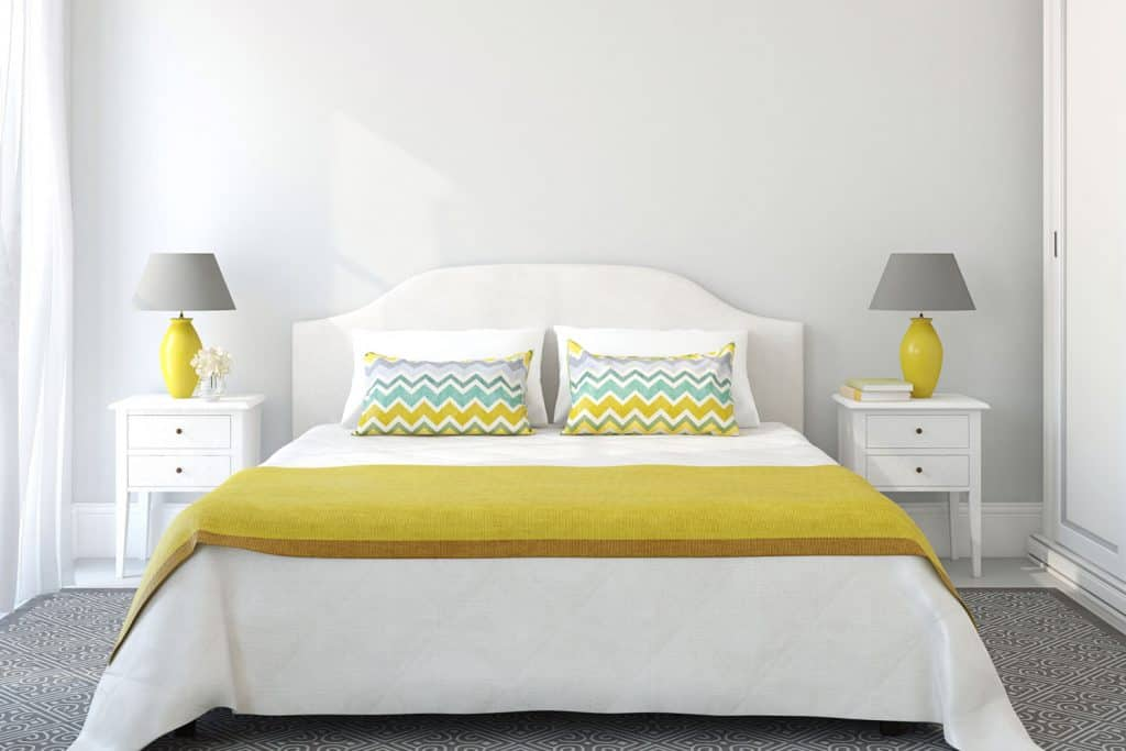 A white bedroom with white yellow and blue stripped pillows, a yellow bedsheet, and gray lamps on each nightstand