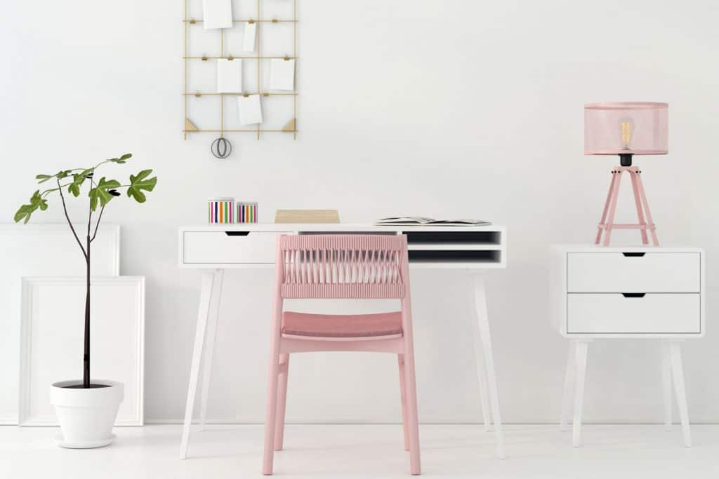 A white living room with an office area with a white computer table and a pink chair