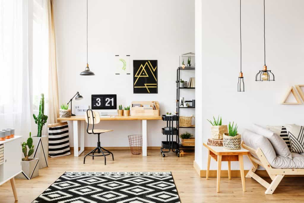 A white living room with an office area on the side with and industrial theme to the area