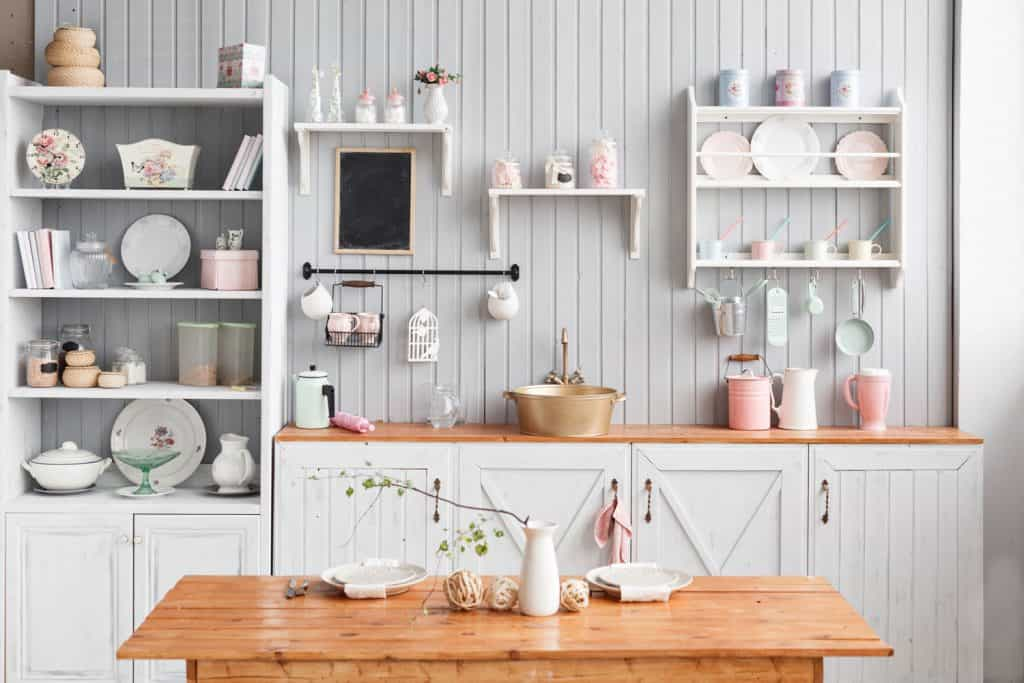 A white themed kitchen counter with white paneled wooden wall and cabinets filled with kitchen utensils
