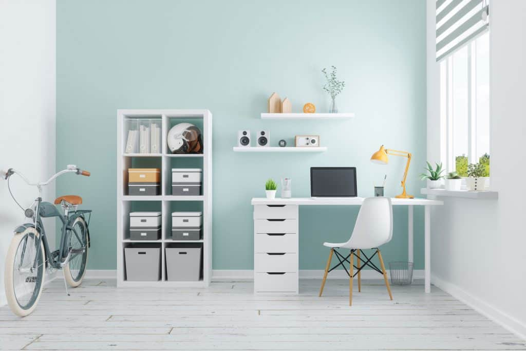 A white themed office area with a white working table and cabinet, and indoor plants on the side