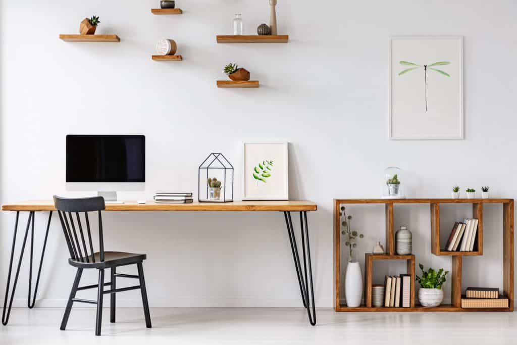 A white themed working area of a luxurious house and a working table with a laptop on it