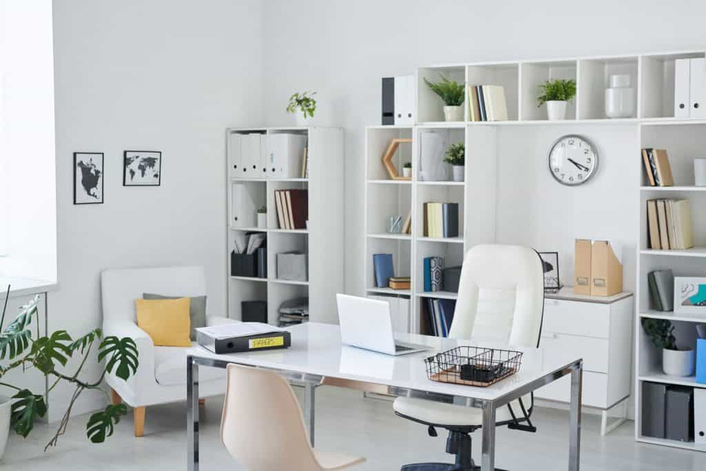 A white office area with a white couch, book shelf on the back with books and files, and a white ceramic table in the front