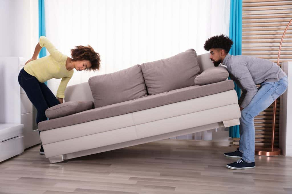 A woman experiencing backpain due to lighting a heavy couch