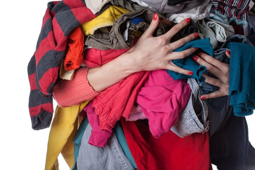 A woman holding piles of unclean laundry