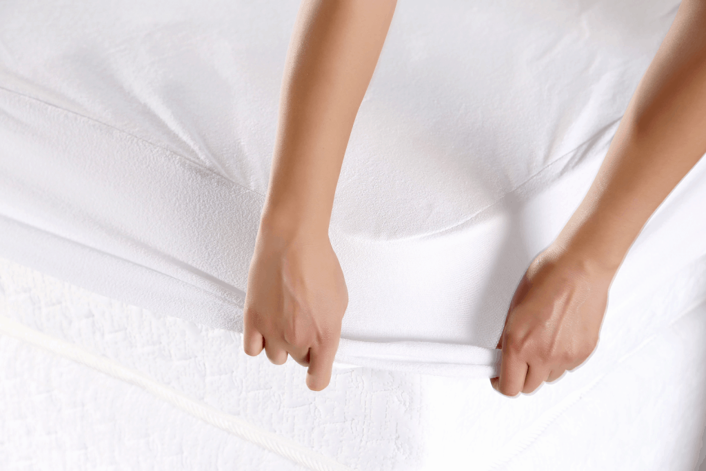 A woman making the bed with white sheets
