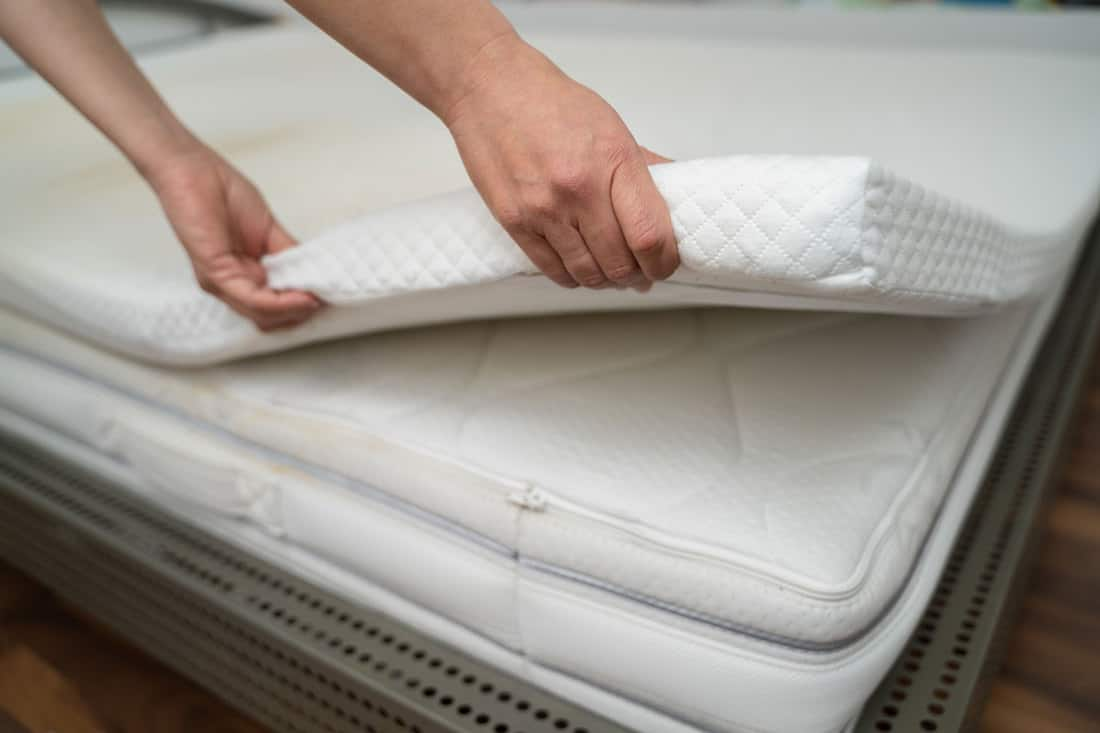 A woman putting on a mattress topper on her room, 7 Types of Mattress Toppers [and How To Choose The Best One]