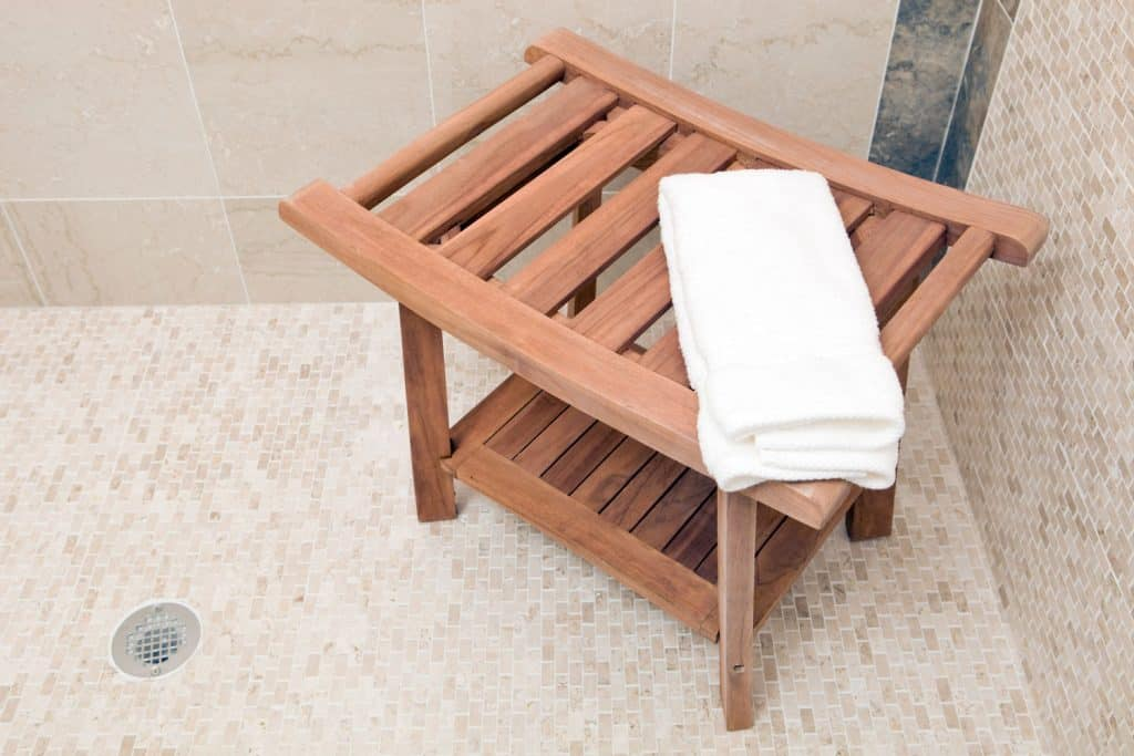 A wooden shower bench with a folded towel on top inside a tiled bathroom