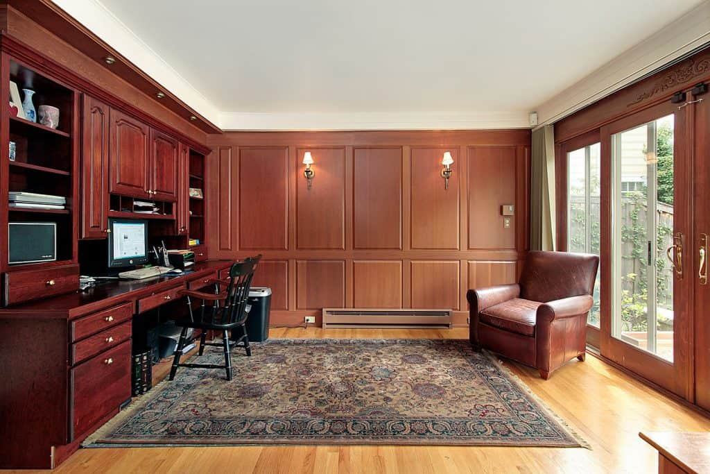A work area with wooden paneled, cabinetry, laminated flooring, and a patterned rug
