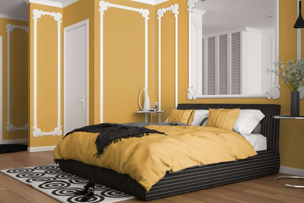 A yellow bedroom with classic floral designs mixed with yellow beddings and a huge mirror on the background