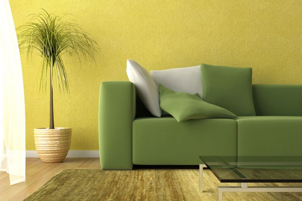 A yellow painted living room with a green couch and green throw pillows