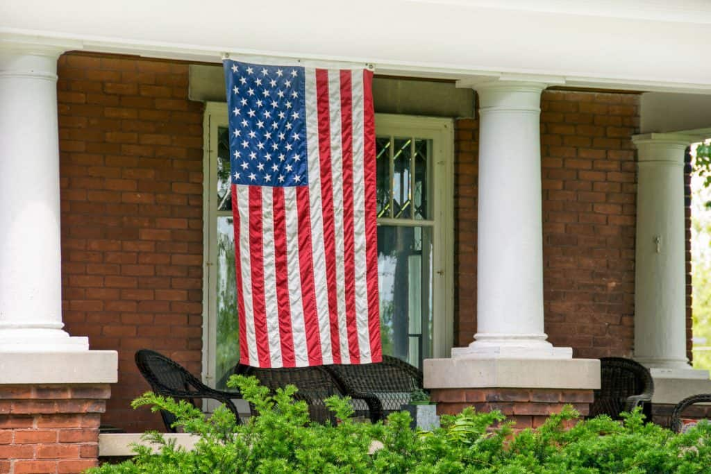 An American Flag suspended on a rope at the front porch