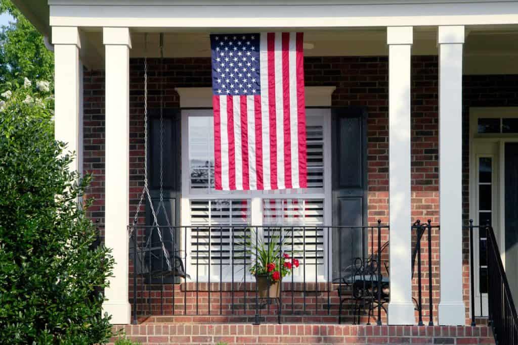 An American Flag suspended on the front porch of a yard