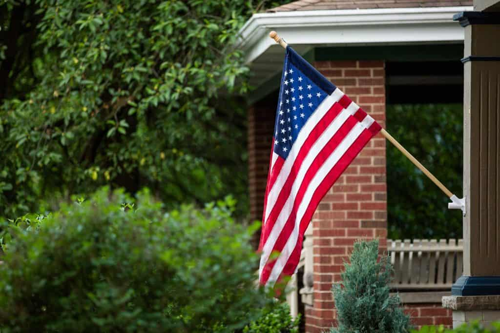 An American flag suspended on a pole displayed at the porch