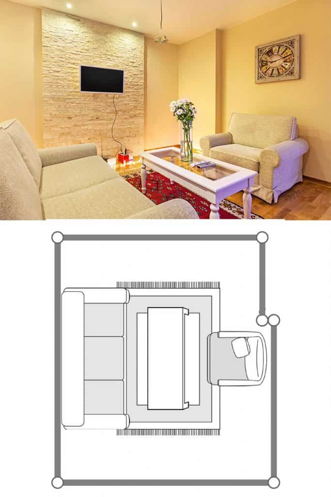 An Egyptian themed living room with a decorative accent wall with a TV on it, two sleeper couches with a coffee table on the middle