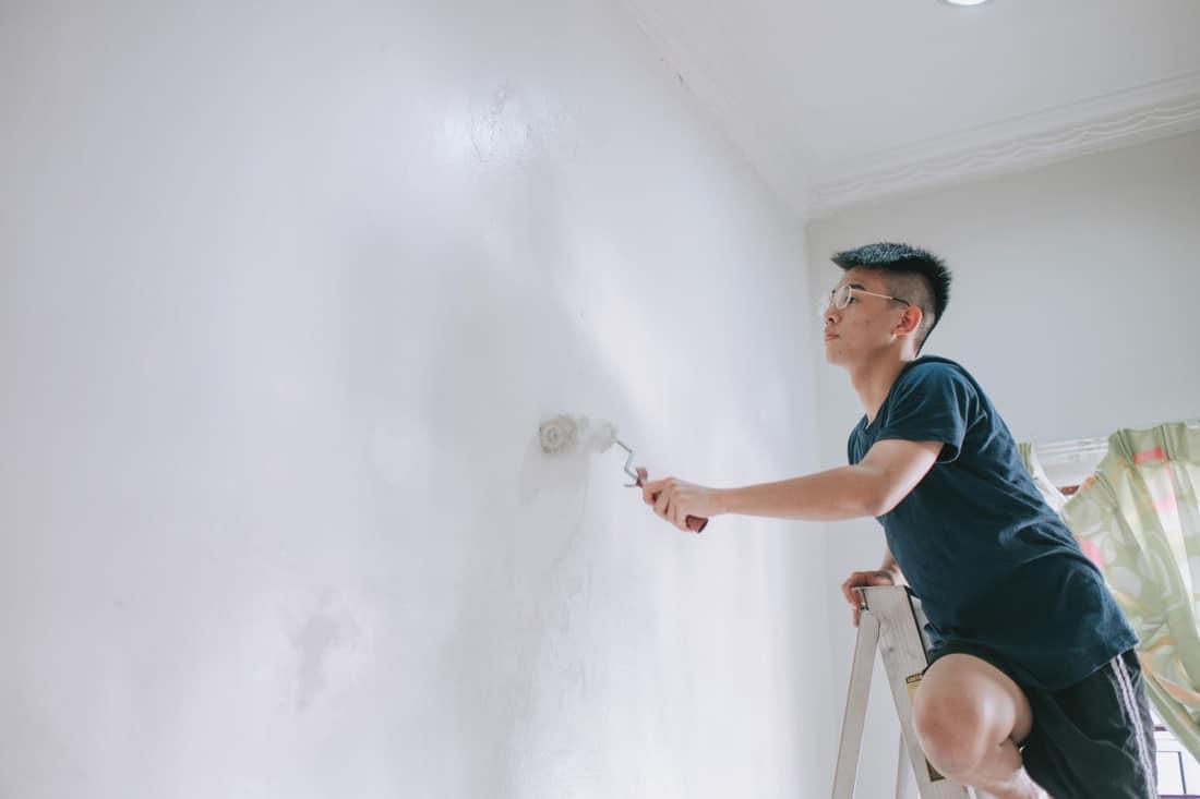 An asian teenage boy painting his bedroom