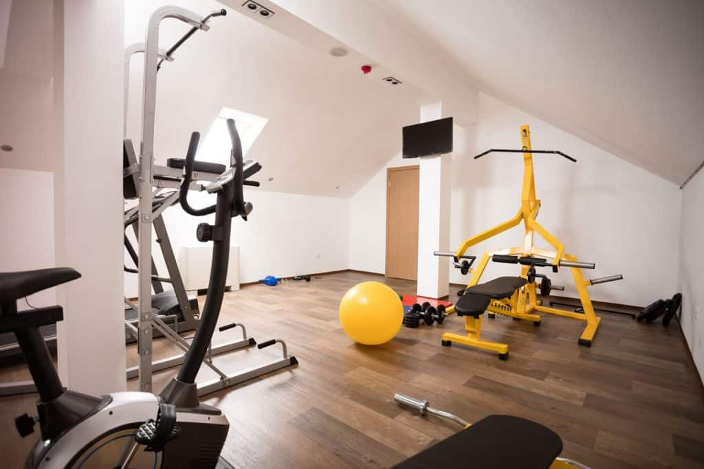 An Attic gym with gym equipment's placed all over the room