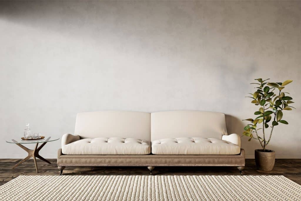 An off white colored wall with a dark wooden flooring and a cream colored couch