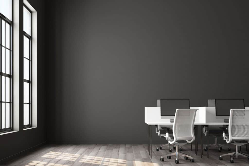 An office with dark gray walls and white cubicles with monitors and white chairs