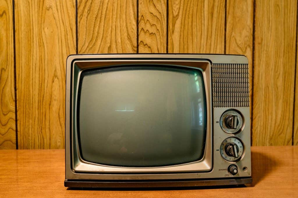 An old 60s styled television placed to a wooden paneled walls