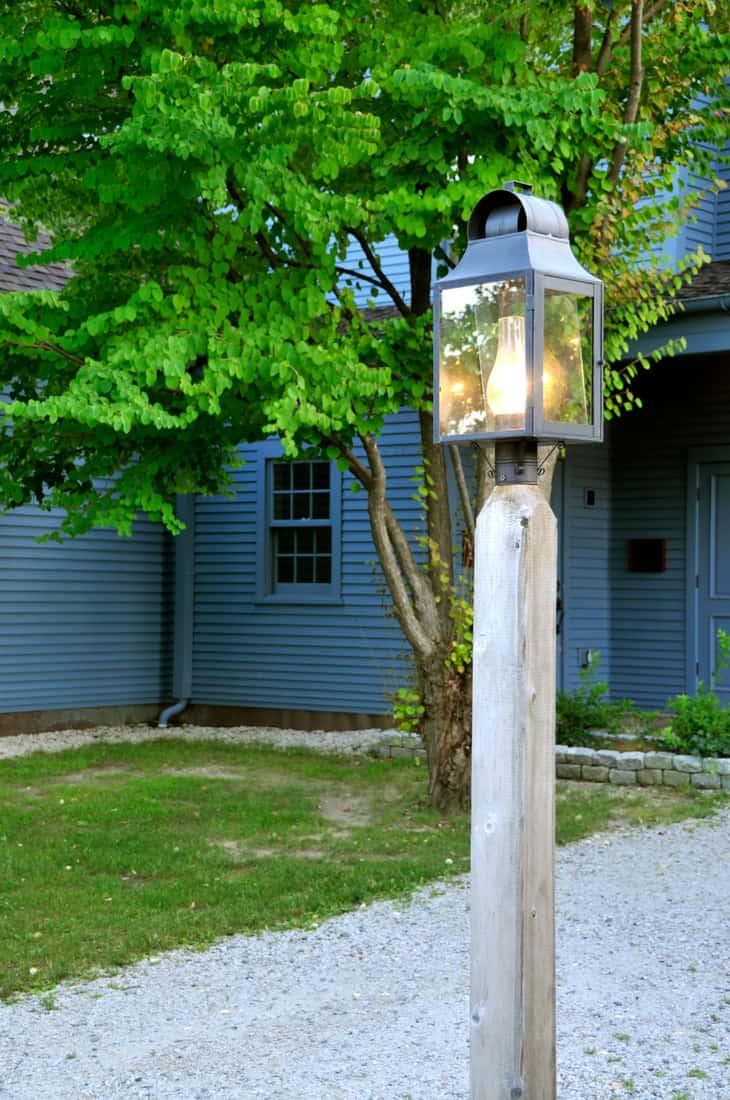 An old fashioned lamp post against the blue house