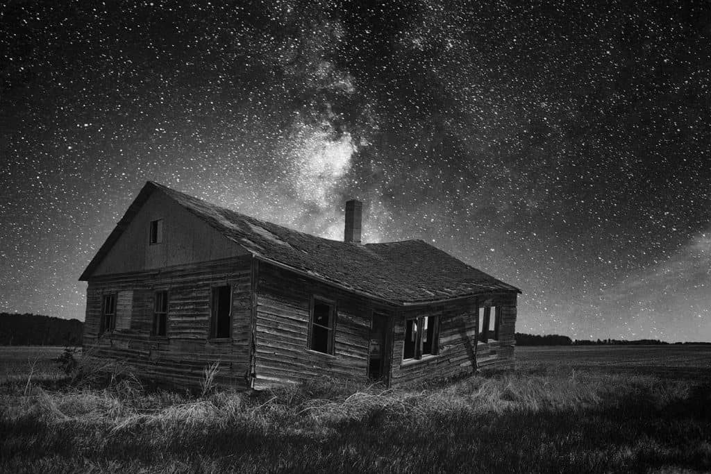 An old weathered and faded clapboard farmhouse sagging in the middle under a starry night sky
